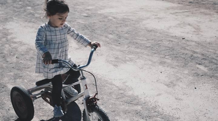 Niña montando en triciclo sin ayuda