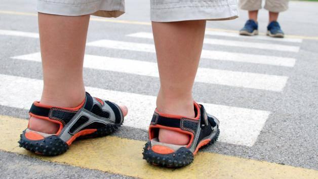 Niño en un paso de peatones esperando a cruzar