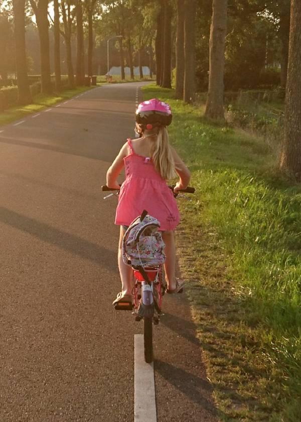 Niña en bicicleta circulando correctamente por la derecha